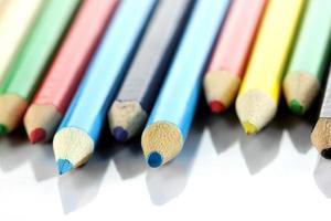 mehrere farbige Buntstifte sind auf Weiß angeordnet.