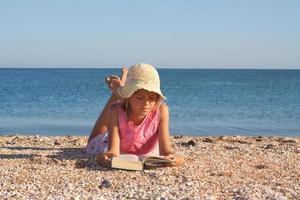 Mädchen liest ein Buch am Strand