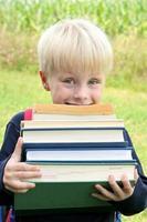 kleines Kind, das viele große schwere Schulbücher trägt foto