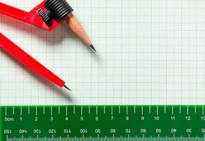 Zeichnen von Kompassen und Lineal auf grünem Millimeterpapier foto