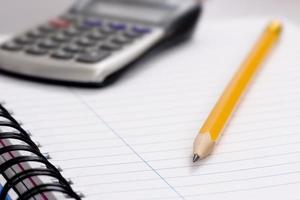 Bleistift und Taschenrechner auf Notizbuch foto