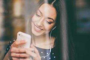 schönes Mädchen, das Musik am Telefon mit Kopfhörern hört foto