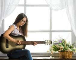 junges Studentenmädchen, das Musik auf Gitarre spielt foto