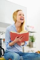 lächelndes Teenager-Mädchen, das Buch in der Küche liest foto