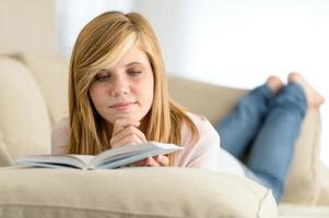 junges Studentenmädchen, das Buch auf Sofa liest foto