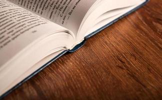 öffne ein großes Buch auf einem Holztisch foto