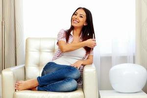 lächelnde Frau, die auf dem Sofa sitzt foto