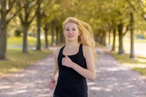 junge blonde Frau, die auf einem Weg mit großen Bäumen joggt foto