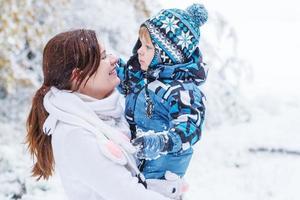 kleiner Vorschulkind und seine Mutter spielen mit dem ersten Schnee foto