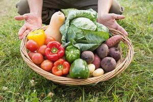 Bauer trägt Korb mit Gemüse