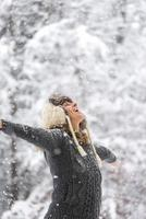 glückliche Frau beim fallenden Schnee mit offenen Armen