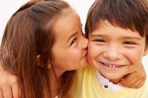 Porträt des hispanischen Mädchens, das Jungen küsst foto