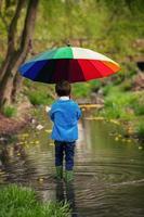 süßer kleiner Junge, der im Regen in einem Teich spazieren geht foto