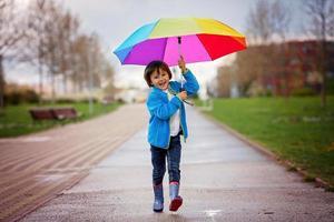 süßer kleiner Junge, der an einem regnerischen Tag in einem Park spazieren geht foto