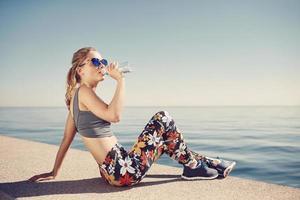 Trinkwasser der jungen Fitnessblondine nach dem Laufen am Strand. foto