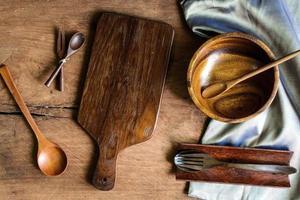 Holzutensilien in der Küche auf altem hölzernen Hintergrund