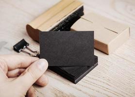 Mann hält schwarze Visitenkarte. Satz leere Büroelemente foto