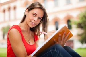 lächelnder Student, der draußen studiert foto