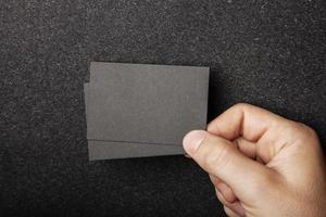 männliche Hand, die zwei schwarze Visitenkarten auf der Dunkelheit hält foto