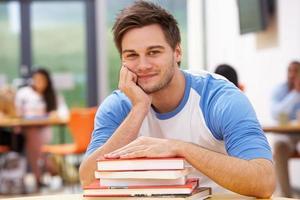 männlicher Student, der im Klassenzimmer mit Büchern studiert foto