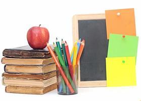 alte Bücher mit Äpfeln und Notizen an kleiner Tafel
