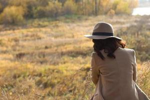 Mädchen in Mantel und Hut sitzt und schaut in die Ferne foto