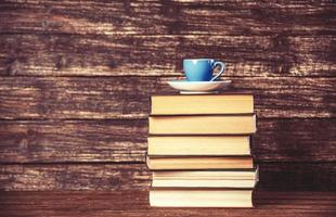Bücher und Tasse Kaffee auf hölzernem Hintergrund.