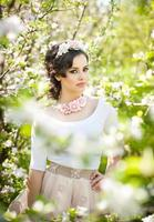 schönes Mädchen, das draußen mit Blumen der Kirschbäume aufwirft foto
