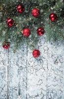 Zweige eines Weihnachtsbaumes auf alten Brettern. fallender Schnee