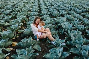 Mutter und Tochter auf dem Feld mit Kohl foto