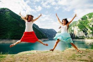 zwei Mädchen springen glücklich in die Berge foto