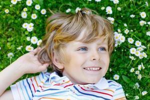 glücklicher Kinderjunge, der auf grünem Gras im Sommer liegt foto