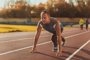 sportlicher Mann, der in der Haltung steht, die bereit ist zu laufen foto