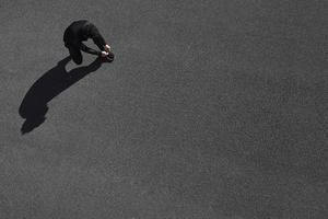 Mann Läufer, der Laufschuhe vor dem Training im Freien bindet. foto