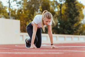 Frau, die in der Startposition für den Lauf steht foto