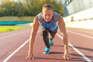 sportlicher Mann, der in der Haltung steht, die bereit ist, auf dem Laufband zu laufen. foto