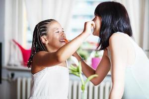 Mutter und Tochter putzen die Zähne foto