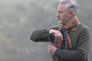 Mann mit Rechen, der in den Nebel schaut