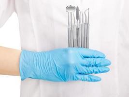 Hand in blauen Handschuh mit zahnärztlichen Werkzeugen foto
