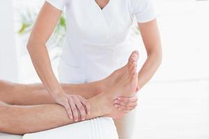 Physiotherapeut macht Fußmassage foto