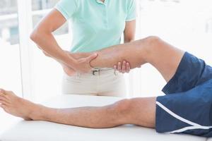 Arzt untersucht Mann Bein foto