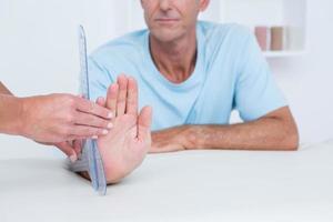 Arzt misst Handgelenk mit Goniometer foto