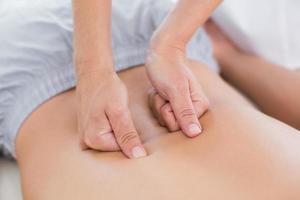 Physiotherapeutin, die ihrer Patientin eine Rückenmassage macht foto