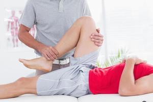 Physiotherapeut macht seinem Patienten eine Beinmassage