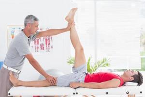 Physiotherapeut, der seinem Patienten das Bein streckt foto