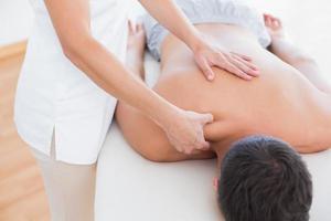 Physiotherapeutin, die ihrer Patientin eine Schultermassage macht foto