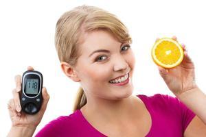 glückliche Frau, die Glukometer und frische Orange hält und Zuckergehalt prüft foto
