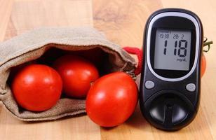 Tomaten in Jutesack und Glukometer auf Holzoberfläche foto
