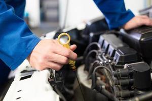 Mechaniker prüft Öl im Auto foto