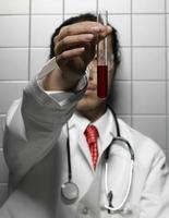 Arzt schaut auf Reagenzglas foto